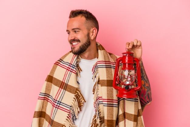 Młody kaukaski mężczyzna z tatuażami trzymający vintage latarnię na białym tle na różowym tle wygląda na bok uśmiechnięty, wesoły i przyjemny.