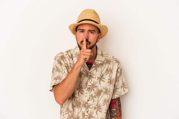 Młody kaukaski mężczyzna z tatuażami, ubrany w letnie ubrania na białym tle, dochowując tajemnicy lub prosząc o ciszę.