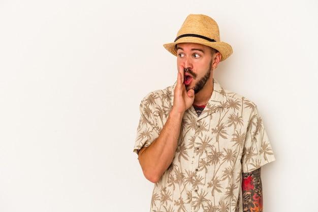 Młody kaukaski mężczyzna z tatuażami, ubrany w letnie ubrania na białym tle, mówi tajne gorące wiadomości o hamowaniu i patrzy na bok