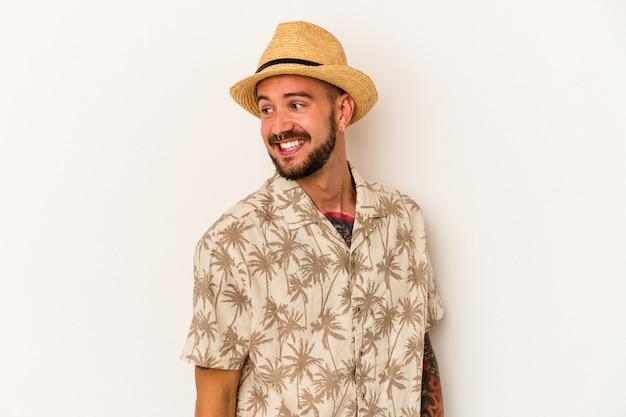 Młody kaukaski mężczyzna z tatuażami ubrany w letnie ubrania na białym tle wygląda z boku uśmiechnięty, wesoły i przyjemny.