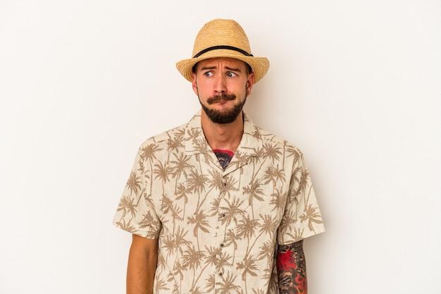 Młody kaukaski mężczyzna z tatuażami, ubrany w letnie ubrania na białym tle zdezorientowany, czuje się niepewny i niepewny.