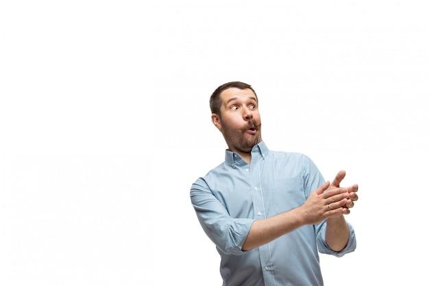 Młody kaukaski mężczyzna z zabawnymi, niezwykłymi popularnymi emocjami i gestami na białym tle