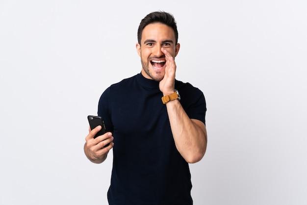 Młody kaukaski mężczyzna za pomocą telefonu komórkowego na białym tle na białej ścianie krzycząc z szeroko otwartymi ustami