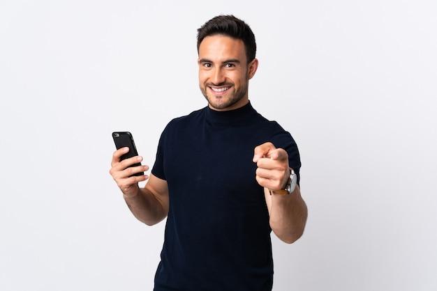 Młody kaukaski mężczyzna za pomocą telefonu komórkowego na białym tle na białej ścianie wskazuje palcem na ciebie z pewną siebie