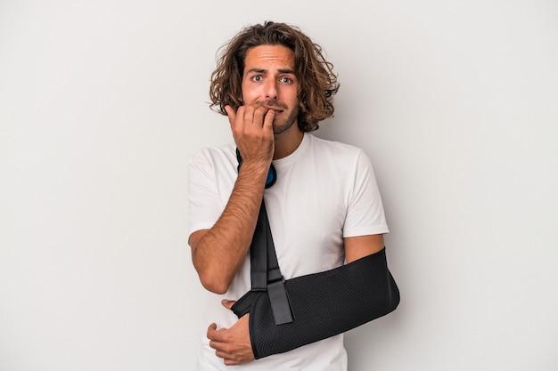 Młody kaukaski mężczyzna ze złamaną ręką na białym tle na szarym tle gryzie paznokcie, nerwowy i bardzo niespokojny.