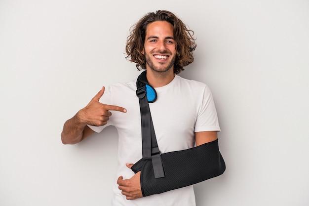 Młody kaukaski mężczyzna ze złamaną ręką odizolowaną na szarym tle osoba wskazująca ręcznie na miejsce na koszulkę, dumna i pewna siebie