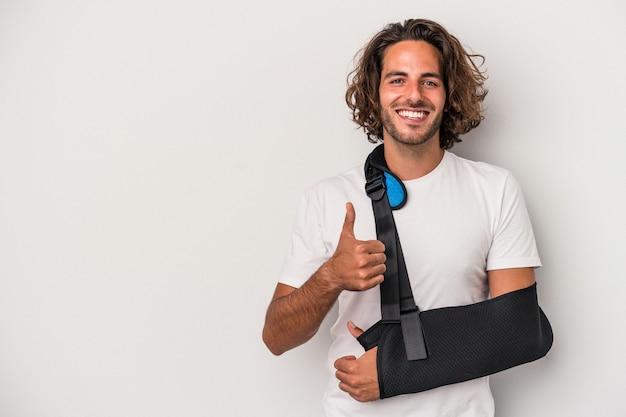 Młody kaukaski mężczyzna ze złamaną ręką odizolowaną na szarym tle uśmiechający się i podnoszący kciuk w górę