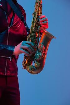 Młody kaukaski muzyk jazzowy grający na saksofonie na gradientowym niebiesko-fioletowym tle studio w świetle neonowym. pojęcie muzyki, hobby, festiwalu. radosny atrakcyjny facet. kolorowy portret artysty.