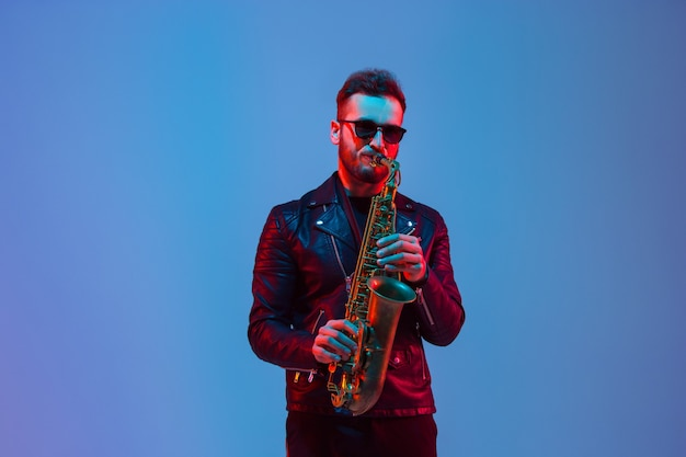 Młody kaukaski muzyk jazzowy grający na saksofonie w gradientowym niebiesko-fioletowym studiu w neonowym świetle