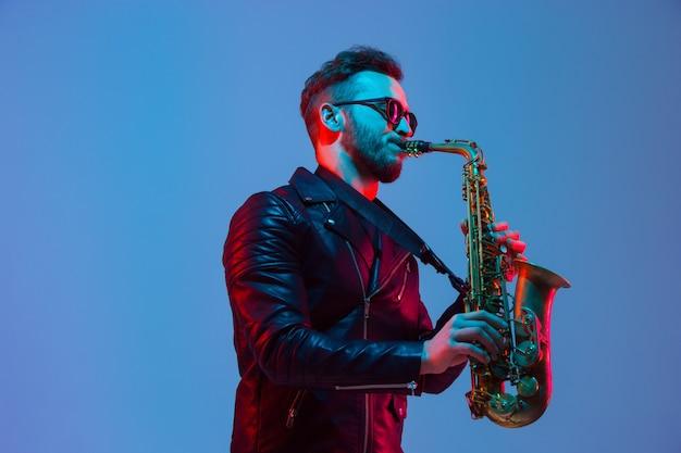 Młody kaukaski muzyk jazzowy grający na saksofonie w studio gradientowym bluepurple