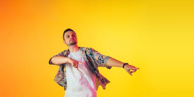 Młody kaukaski muzyk tancerz gospodarz imprezy dj na gradientowym tle w świetle neonowym