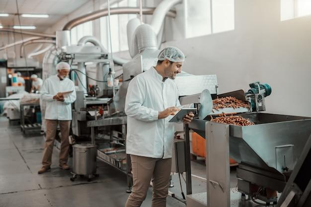 Młody kaukaski nadzorca oceniający jakość żywności w roślinie spożywczej trzymając tabletkę. mężczyzna jest ubrany w biały mundur i ma siatkę na włosy.