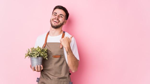 Młody kaukaski ogrodnik mężczyzna trzyma roślinę odizolowane punkty z dala od kciuka, śmiejąc się i beztrosko.