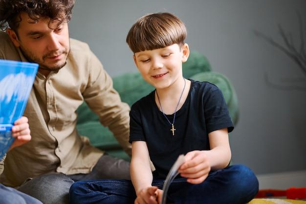Młody kaukaski ojciec spędzający czas w domu z synami i czytając książki na podłodze. szczęśliwy rodzic bawiący się z dziećmi w wieku przedszkolnym. koncepcja edukacji domowej