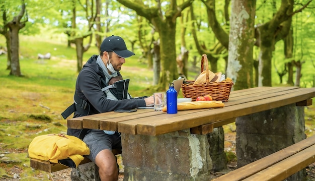 Młody kaukaski ojciec telepracy siedzi przy stole piknikowym z komputerem w lesie