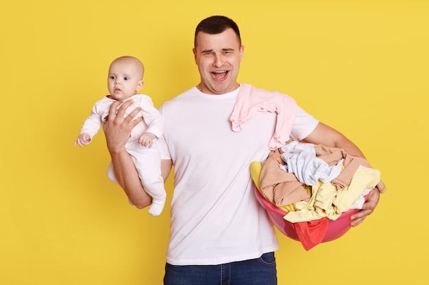 Młody kaukaski ojciec z noworodkiem. rodzic człowiek przewożący dziecko stojąc na białym tle nad żółtą ścianą. samotny tata krzyczy coś podczas wykonywania prac domowych na urlopie ojcowskim.