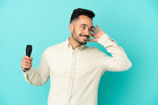 Młody kaukaski piosenkarz na białym tle na niebieskim tle, słuchając czegoś, kładąc rękę na uchu