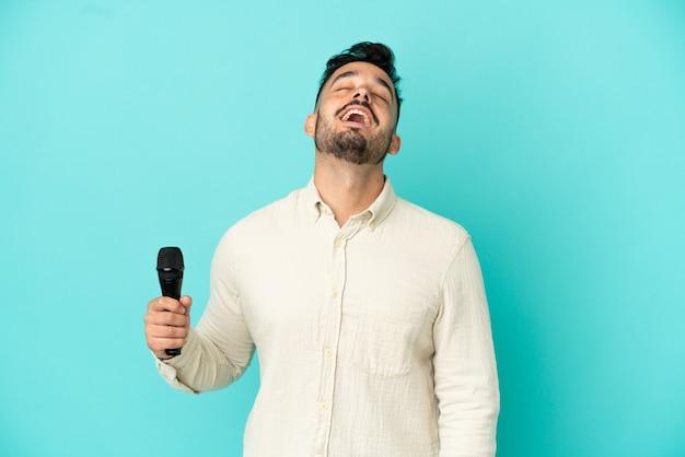 Młody kaukaski piosenkarz na białym tle na niebieskim tle śmiejąc się
