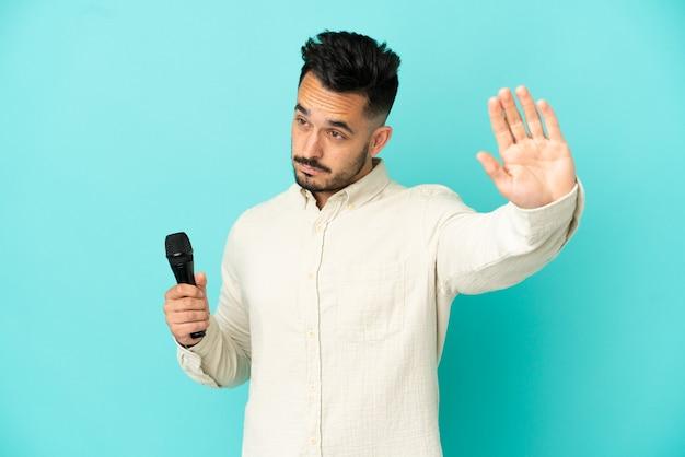 Młody kaukaski piosenkarz na białym tle na niebieskim tle, wykonując gest zatrzymania i rozczarowany