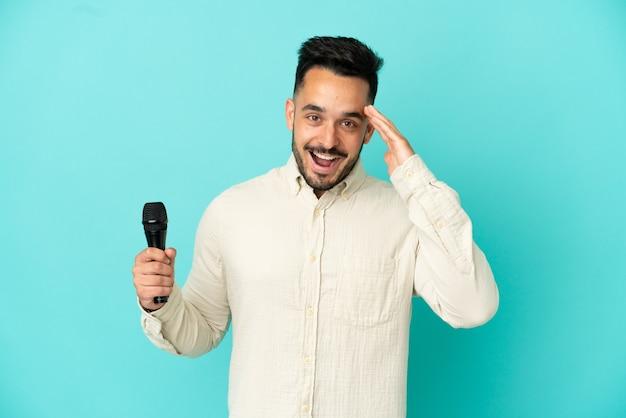 Młody kaukaski piosenkarz na białym tle na niebieskim tle z zaskoczeniem i zszokowanym wyrazem twarzy
