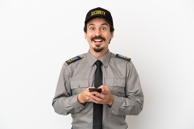 Młody kaukaski pracownik ochrony na białym tle zaskoczony i wysyłający wiadomość
