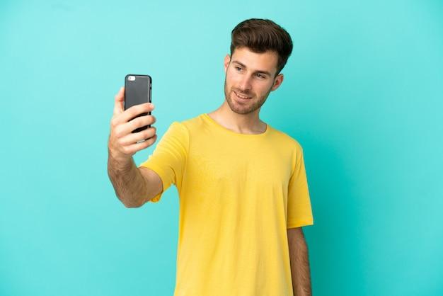 Młody kaukaski przystojny mężczyzna na białym tle na niebieskim tle robi selfie