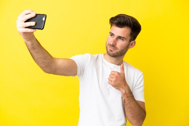 Młody kaukaski przystojny mężczyzna na białym tle na żółtym tle robi selfie z telefonem komórkowym
