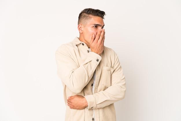 Młody kaukaski przystojny mężczyzna na białym tle ziewanie pokazując zmęczony gest obejmujący usta ręką.
