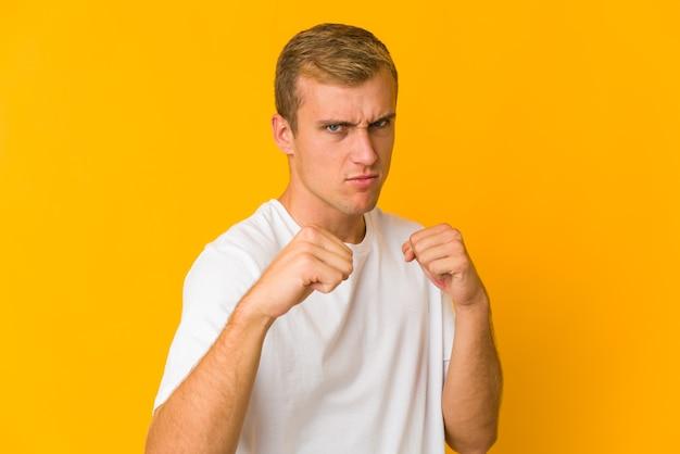Młody kaukaski przystojny mężczyzna rzuca cios, złość, walka z powodu kłótni, boks.