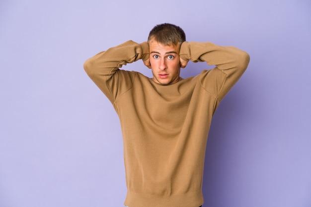 Młody kaukaski przystojny mężczyzna zakrywający uszy rękami, starając się nie słyszeć zbyt głośnego dźwięku.