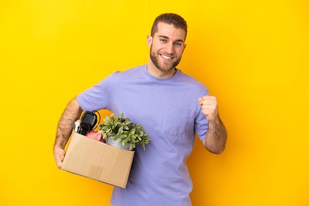 Młody kaukaski robi krok, podnosząc pudełko pełne rzeczy na żółtej ścianie, świętując zwycięstwo