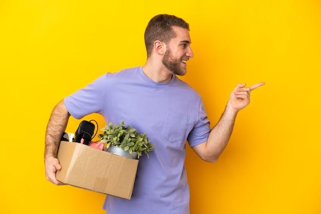 Młody kaukaski robi krok, podnosząc pudełko pełne rzeczy na żółtej ścianie wskazując palcem w bok i prezentując produkt