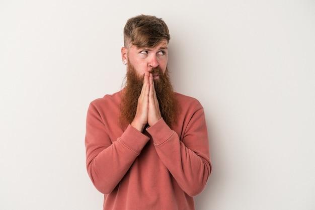 Młody kaukaski rudy mężczyzna z długą brodą na białym tle modlący się, okazujący oddanie, religijny człowiek szukający boskiej inspiracji.