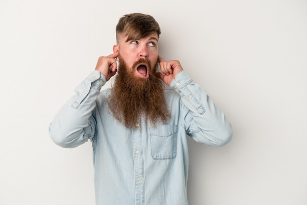 Młody kaukaski rudy mężczyzna z długą brodą na białym tle zakrywającym uszy palcami, zestresowany i zdesperowany przez głośne otoczenie.