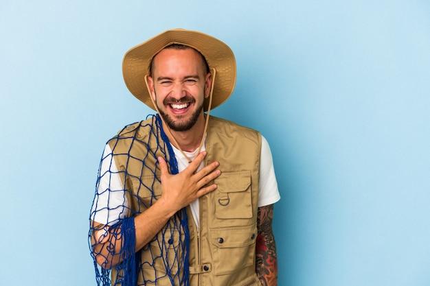 Młody kaukaski rybak z tatuażami trzymający siatkę na białym tle na niebieskim tle śmieje się głośno trzymając rękę na klatce piersiowej.
