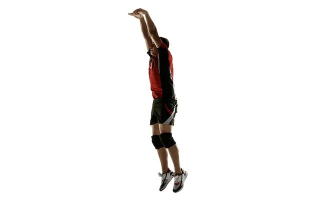 Młody kaukaski siatkarz platicing na białym tle na białej ścianie. męski sportowiec trening z piłką w ruchu i akcji. sport, zdrowy styl życia, aktywność, koncepcja ruchu. miejsce.