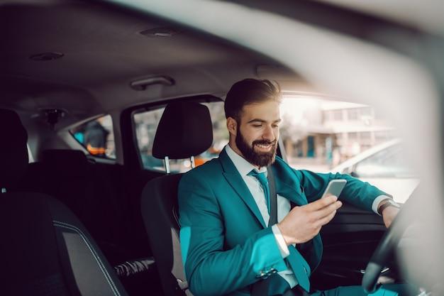 Młody kaukaski sukces brodaty biznesmen w turkusowym garniturze iz uśmiechem toothy siedzi w samochodzie i za pomocą inteligentnego telefonu. ekspert we wszystkim był kiedyś początkującym.