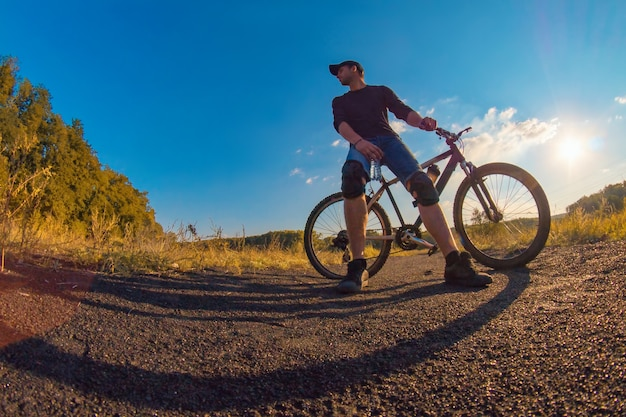 Młody kaukaski wysportowany mężczyzna w nakolannikach polega na sportowym rowerze i wpatruje się w dal na kolorową jesień z jasnym błękitnym niebem.