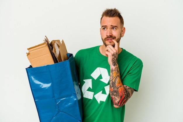 Młody kaukaski wytatuowany mężczyzna poddany recyklingowi karton na białym tle zrelaksowany myślenie o czymś, patrząc na przestrzeń kopii.