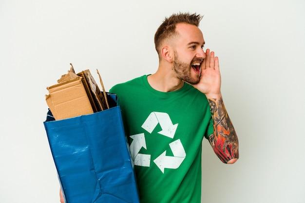 Młody kaukaski wytatuowany mężczyzna z recyklingu kartonu na białym tle krzycząc i trzymając dłoń w pobliżu otwartych ust.