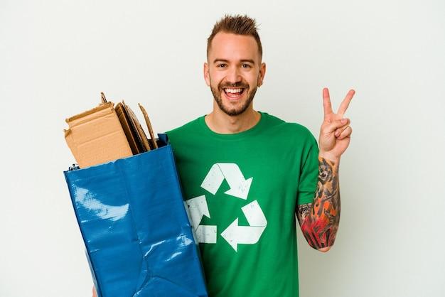 Młody kaukaski wytatuowany mężczyzna z recyklingu kartonu na białym tle radosny i beztroski przedstawiający palcami symbol pokoju.