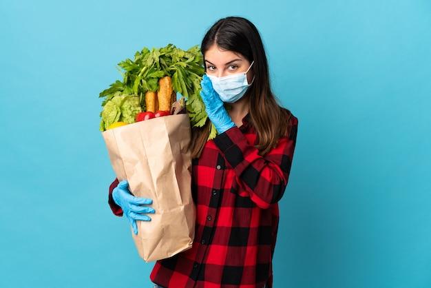 Młody kaukaski z warzywami i maską na białym tle na niebieskiej ścianie coś szepcząc