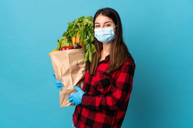 Młody kaukaski z warzywami i maską na białym tle na niebieskiej ścianie dużo się uśmiecha