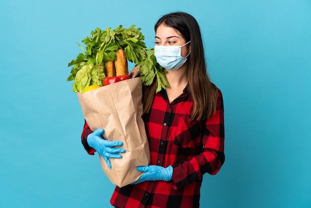 Młody kaukaski z warzywami i maską na białym tle na niebieskiej ścianie z happy wypowiedzi