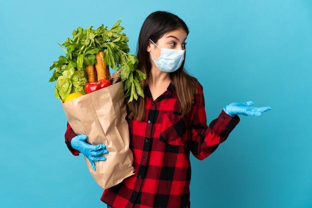 Młody kaukaski z warzywami i maską na białym tle na niebieskiej ścianie z wyrazem twarzy zaskoczenia