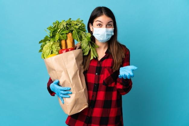 Młody kaukaski z warzywami i maską na białym tle na niebieskiej ścianie z zszokowanym wyrazem twarzy