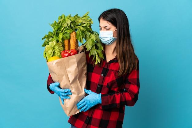 Młody kaukaski z warzywami i maską na białym tle na niebieskiej ścianie ze smutnym wyrazem