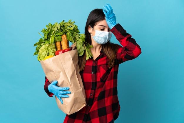Młody kaukaski z warzywami i maską na niebieskiej ścianie coś sobie uświadomił i zamierza znaleźć rozwiązanie