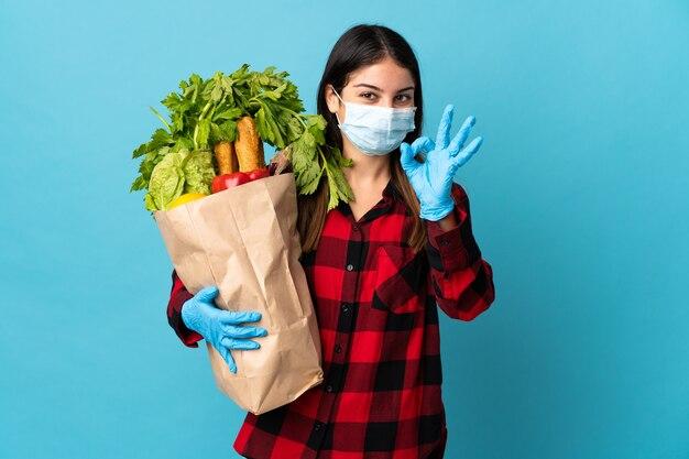 Młody kaukaski z warzywami i maską na niebieskim tle pokazując znak ok palcami