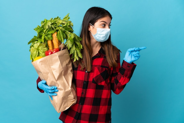 Młody kaukaski z warzywami i maską na niebieskim tle, wskazując na bok, aby przedstawić produkt